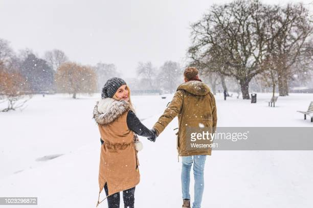 happy teenage girl strolling with her boyfriend in park on snow day - 深い雪 ストックフォトと画像