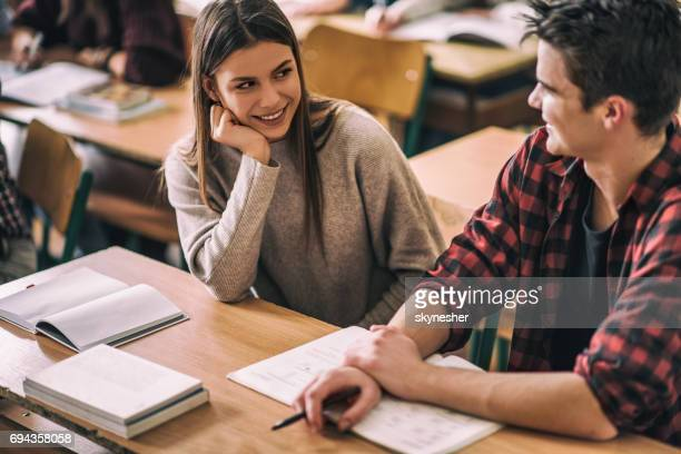 Happy teenage girl talking to her friend on a class.