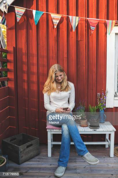 Happy teenage girl using mobile phone while sitting on bench in back yard