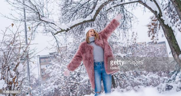 happy teenage girl walking in the park on a cold snowy day. - pink coat stock pictures, royalty-free photos & images