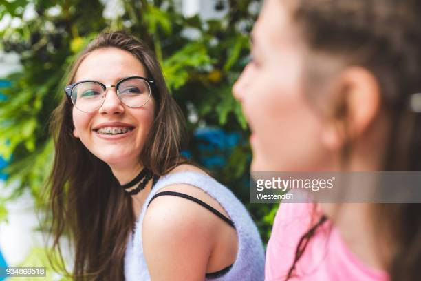 Happy teenage girl with braces and glasses looking at friend