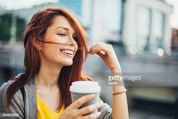 Happy teenage girl with coffee cup