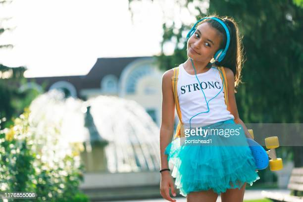 happy teenage girl with skateboard and headphones - new generation stock pictures, royalty-free photos & images