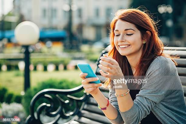 happy teenage girl with smart phone - cabelo pintado de vermelho - fotografias e filmes do acervo