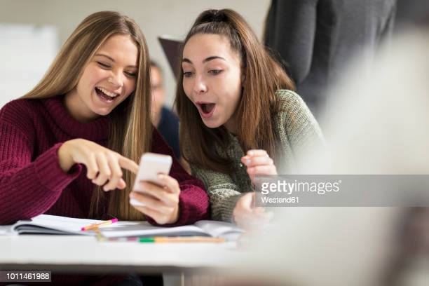 happy teenage girls in class looking at cell phone - online messaging stock pictures, royalty-free photos & images