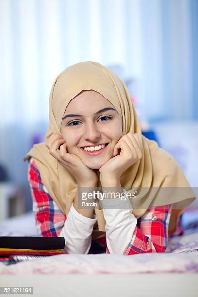 Happy teenage muslim girl lying on bed