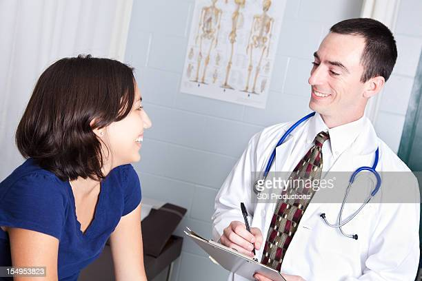 Happy Teenage Patient With Doctor in Doctor's Office