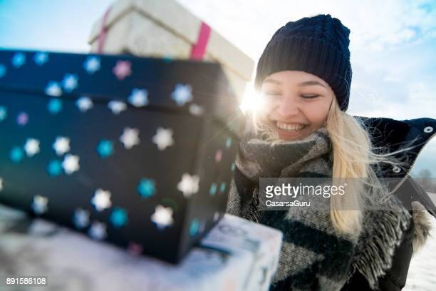 Happy Teenaged Woman With Gifts in Hands Outdoors on Snow