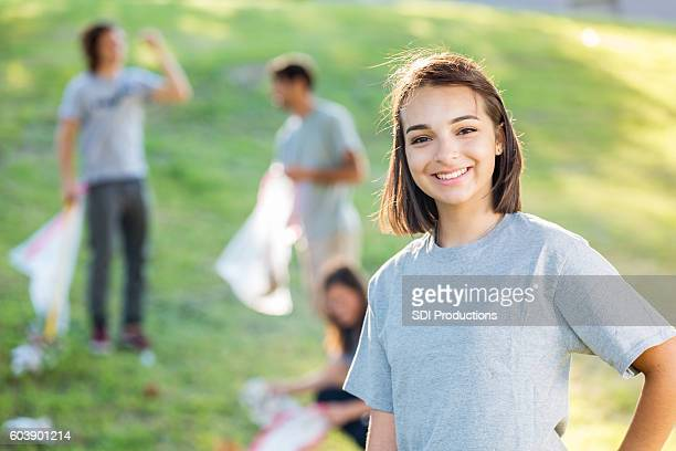 Happy teenager at a park clean up with community volunteers