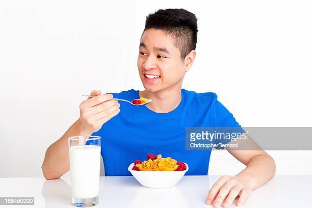 Happy teenager eating breakfast