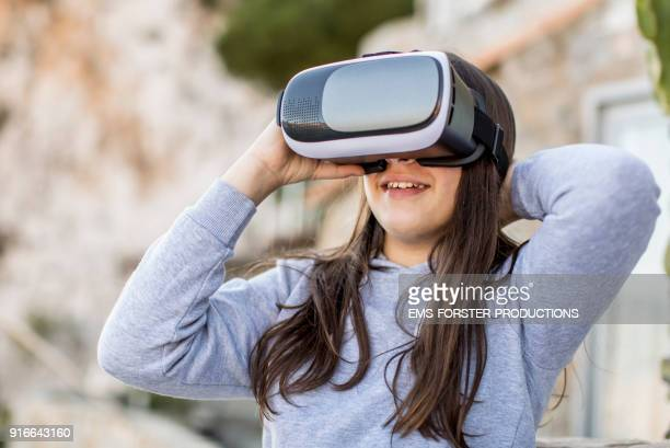 happy, teenager girl using virtual reality headset outdoors