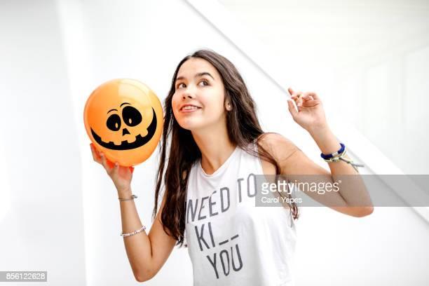 happy teenager holding a orange  pumpkin balloon