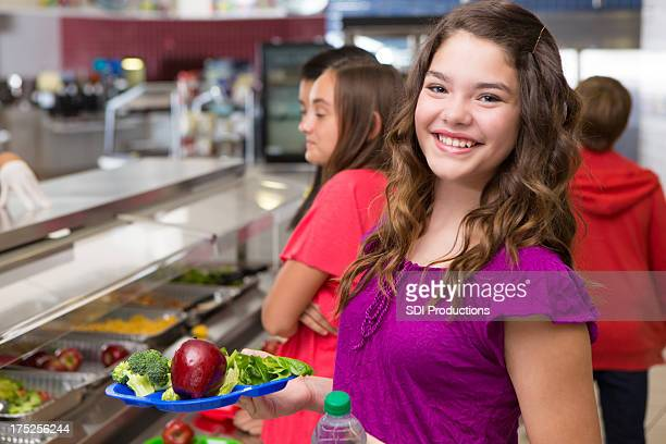 Happy teenager holding her lunch at the school cafeteria