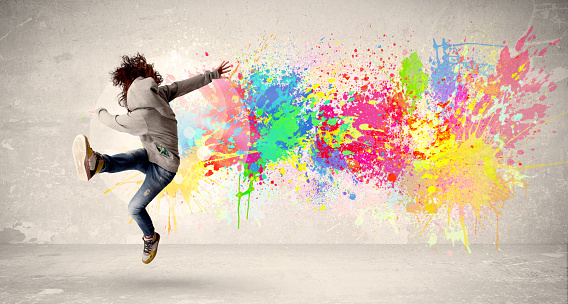 Happy teenager jumping with colorful ink splatter on urban background 925391962