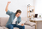 Happy teenager win in online game on tablet