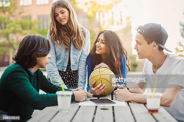 happy teenagers discussing at table outdoors - seulement des adolescents ou adolescentes photos et images de collection