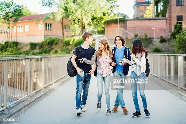 happy teenagers enjoying while walking on bridge - 16 17 ans photos et images de collection