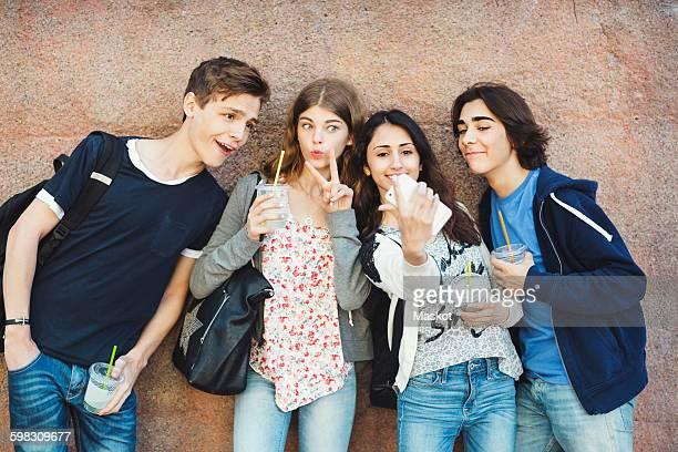 happy teenagers gesturing while taking selfie against wall - friedenszeichen handzeichen stock-fotos und bilder