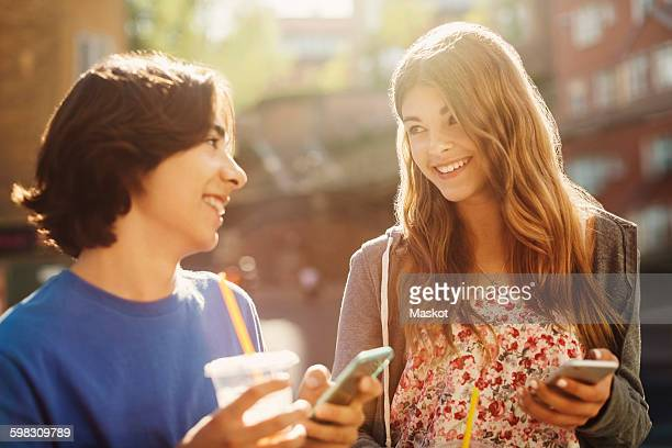 Happy teenagers looking at each other while holding smart phones outdoors