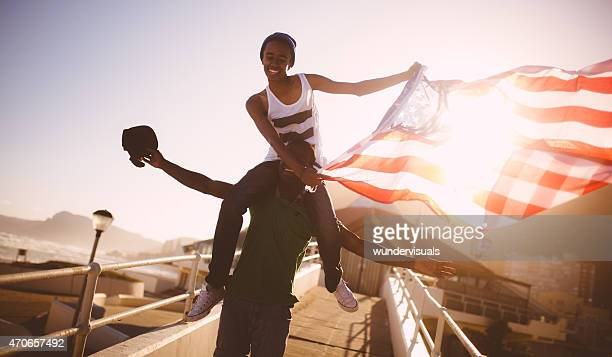 Happy teenagers proudly displaying an American flag