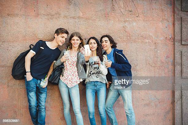 Happy teenagers taking selfie against wall