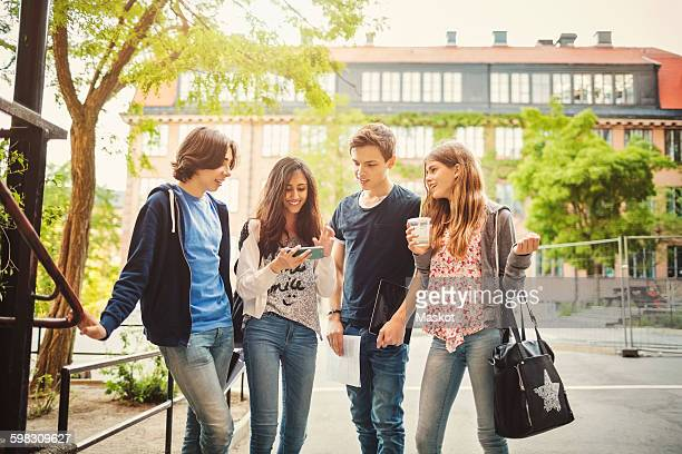 Happy teenagers using smart phone on street