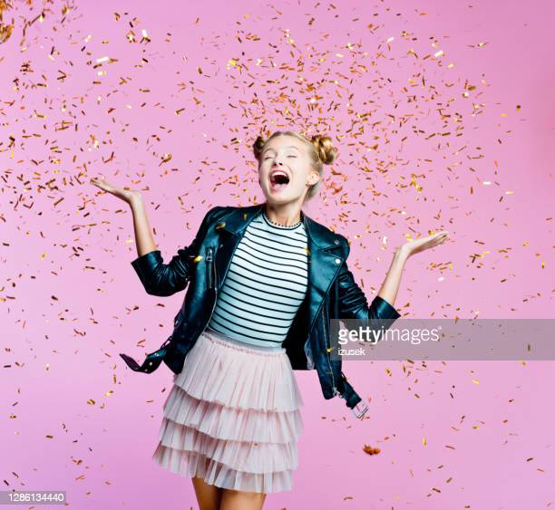 happy teenege girl among gold confetti - embellished jacket stock pictures, royalty-free photos & images
