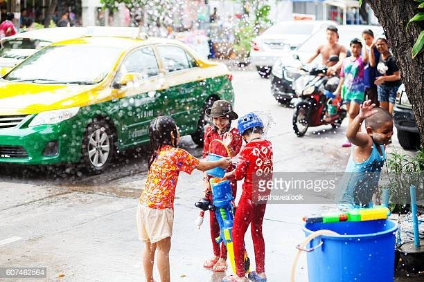 happy thai kids with big water gun - buddhist new year stock pictures, royalty-free photos & images