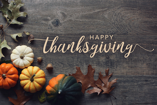 Happy Thanksgiving day greeting text with pumpkins, squash and leaves over dark wood table background 1181113921