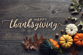 Happy Thanksgiving greeting text with fall pumpkins, squash and leaves over dark wood background