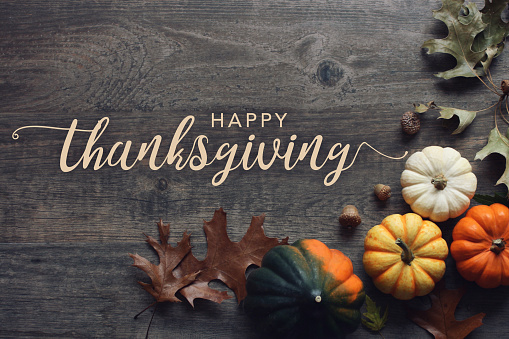Happy Thanksgiving greeting text with fall pumpkins, squash and leaves over dark wood background 1163379073