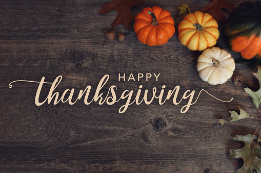 Happy Thanksgiving text with pumpkins and leaves over dark wood background 870456188