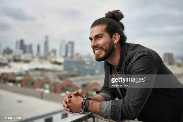 happy thoughtful man with hands clasped in balcony - man bun stock pictures, royalty-free photos & images