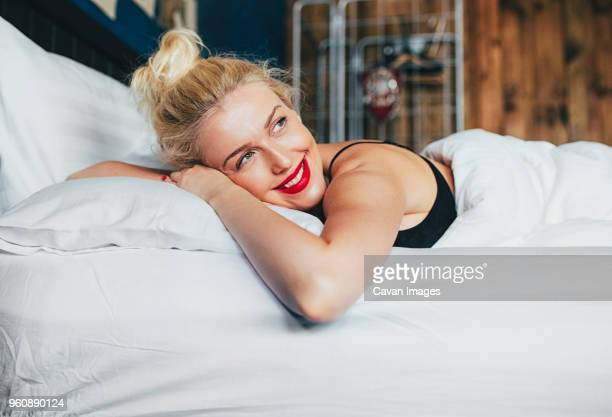 Happy thoughtful woman relaxing on bed at home