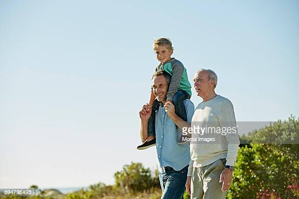 happy three generation males walking on field - grandfather stock pictures, royalty-free photos & images