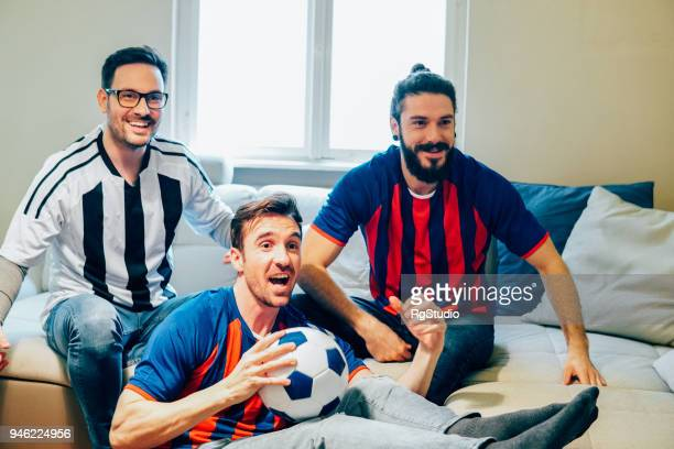 Happy three male friends watching a football game from home