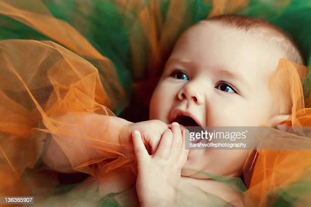 Happy three month old baby girl laying in tulle