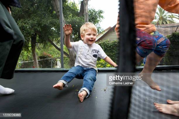 happy toddler bouncing on his bottom on a trampoline with older kids around him - catherine ledner stock pictures, royalty-free photos & images