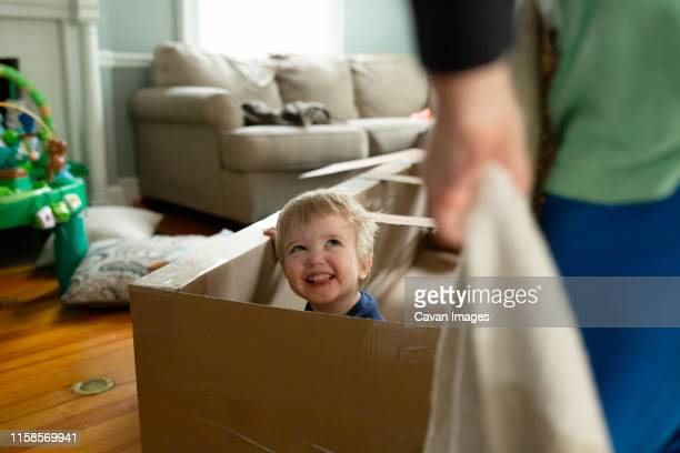 happy toddler boy looks up at brother smiling inside cardboard toy - fort stock pictures, royalty-free photos & images