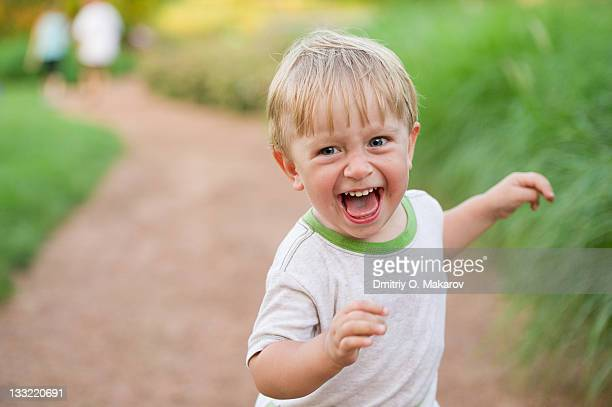Happy toddler boy running in park