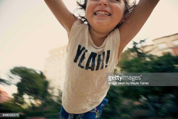 happy toddler flying at the park - extatisch stockfoto's en -beelden