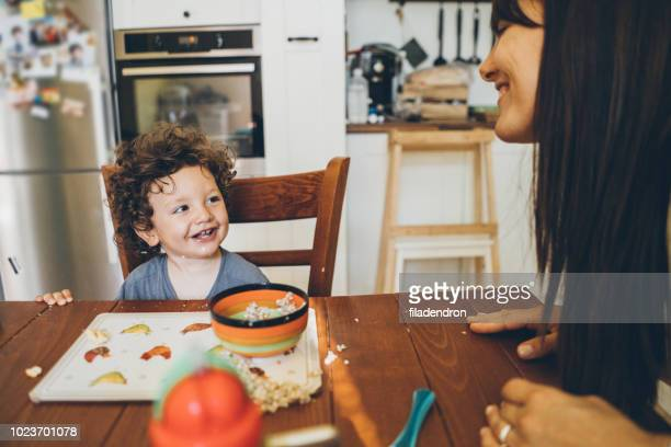 happy toddler making mess - oatmeal stock pictures, royalty-free photos & images