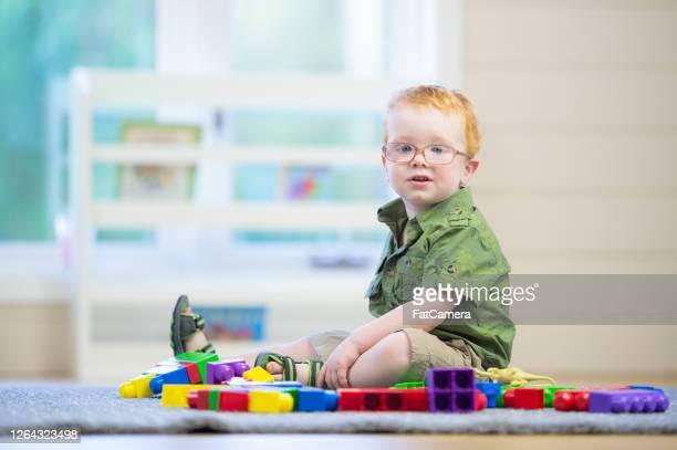 felice bambino sul tappeto - autismo foto e immagini stock