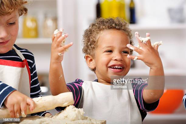 Happy Toddler Showing Off Hands Covered With Dough