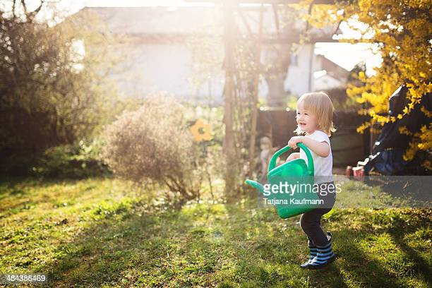 Happy Toddler with Watering Can in Garden