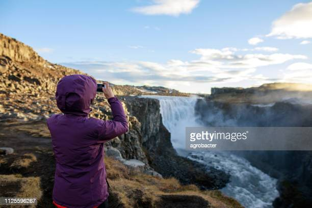 happy tourist against dettifoss waterfall background - dettifoss waterfall stock photos and pictures