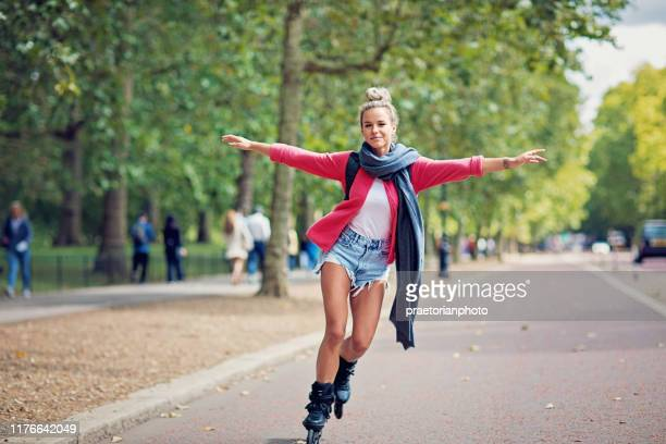 happy tourist girl is skating on the street - roller skating stock pictures, royalty-free photos & images