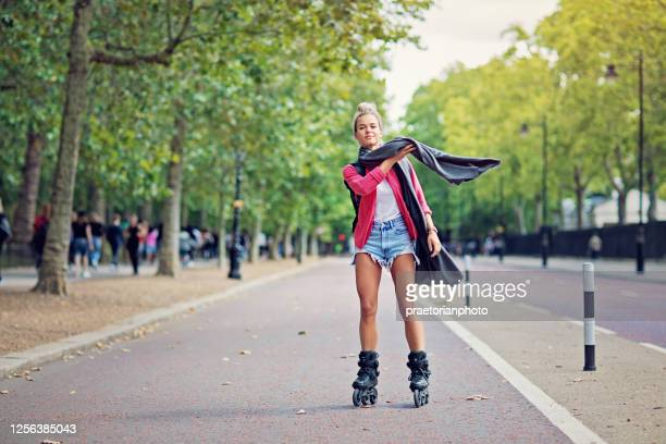 happy tourist girl is skating on the street - boulevard stock pictures, royalty-free photos & images