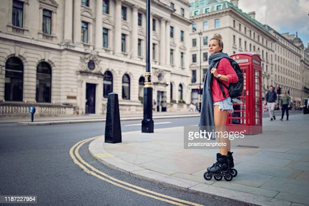 happy tourist girl is skating on the streets of london - looking stock pictures, royalty-free photos & images