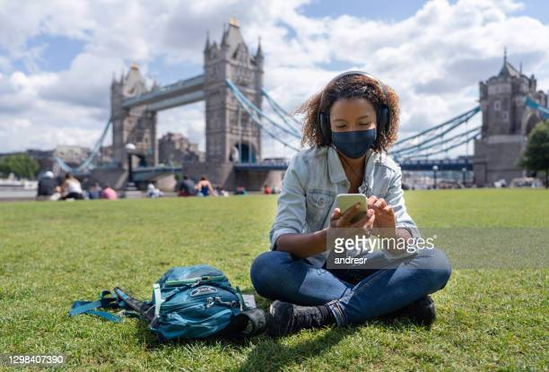 happy tourist in london listening to music outdoors wearing a facemask - state of emergency stock pictures, royalty-free photos & images